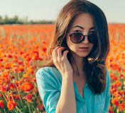 Brunette woman in sunglasses in flowers meadow. Beautiful brunette young woman in sunglasses in spring red poppies flowers meadow, looking at camera stock photos