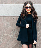 Beautiful brunette young woman with sunglasses wearing fashionable clothes posing on stone background. Royalty Free Stock Photography