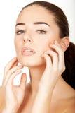 Beautiful brunette young woman using facial creme Stock Photos