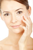 Beautiful brunette young woman using facial creme Stock Photo