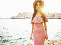 Stylish brunette woman enjoying sunrise on seafront. Beautiful brunette young woman wearing pink dress and straw hat enjoying sunrise on seafront in old european royalty free stock photos