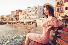 Stylish brunette woman enjoying sunrise on seafront. Beautiful brunette young woman wearing pink dress and straw hat enjoying sunrise on seafront in old european royalty free stock photo