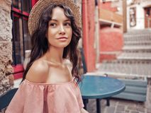 Stylish brunette woman in old town. Beautiful brunette young woman wearing pink dress and straw hat on the street in old european Town. Fashion and style. Summer Stock Photography