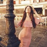 Stylish brunette woman walking in old town. Beautiful brunette young woman wearing pink dress and straw hat walking on the street in old european Town. Fashion Royalty Free Stock Image