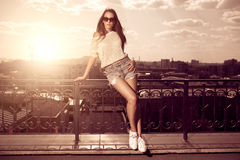 Beautiful brunette young woman wearing sunglasses, shorts, white. Top posing above sunset city background. Hot summer Stock Photo