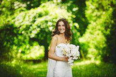 Beautiful brunette young woman with wedding hairstyle in a stylish wedding dress with a white orchid in her hands posing stock image
