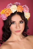 Beautiful brunette young woman with wreath of flowers studio shot pink background Stock Photos