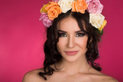 Beautiful brunette young woman with wreath of flowers studio shot pink background Royalty Free Stock Photos