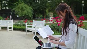 Lady Sitting in the Park, Using Laptop. Data Entry. Beautiful brunnette lady sitting on a white bench in the park and using a laptop. Data entry. Medium shot Stock Photos