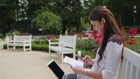 Lady Sitting in the Park and Using Laptop and Phone. Beautiful brunnette lady sitting on a white bench in the park and using a laptop and a telephone. Medium Stock Photo