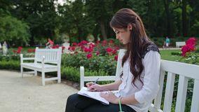 Lady Sitting in the Park and Writing. Beautiful brunnette lady sitting on a white bench in the park and writing. Medium shot Stock Photography