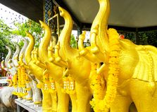 Beautiful buddhist worship temple with golden elephants surrounding the location. royalty free stock photography