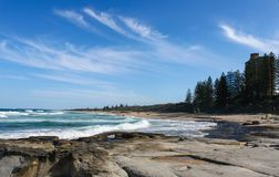 Beautiful Buddina Beach on the Sunshine Coast of Australia with beautiful turquoise water and unidentifiablee people down the beac. H and tall buildings and stock images