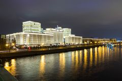 Beautiful building near the river on the background of the city with lights. Evening royalty free stock photos