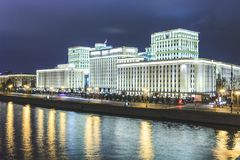 Beautiful building near the river on the background of the city with lights. Evening royalty free stock images