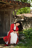 Beautiful Bulgaria. Beautiful young woman in bulgarian national dress peeling an apple in the old village of Jeravna Stock Photography