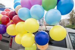 Beautiful bunch of colorful balloons fixed to the roof of the ca Royalty Free Stock Images