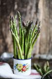A bunch of asparagus in a cup. A beautiful bunch of fresh organic asparagus in an old enamelled mug Royalty Free Stock Photo