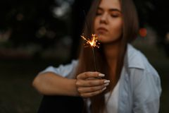 Beautiful burning Bengali fire with sparks in female hands. Beautiful young burning Bengali fire with sparks in female hands stock photo