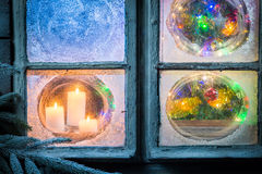 Beautiful burning candles for Christmas in frozen window Royalty Free Stock Images