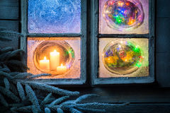 Beautiful burning candles for Christmas in frozen window at eve royalty free stock photography