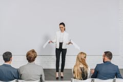 Beautiful business coach standing on stage and gesturing during training. In hub stock image