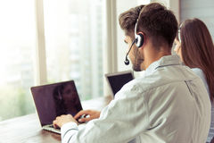 Beautiful business couple working. Back view of handsome young businessman and beautiful business women in headsets using laptops while working in office Stock Image
