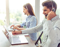Beautiful business couple working. Side view of handsome young businessman and beautiful business women in headsets using laptops while working in office Royalty Free Stock Photos