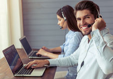 Beautiful business couple working. Side view of handsome young businessman and beautiful business women in headsets using laptops while working in office. Guy is Stock Photo