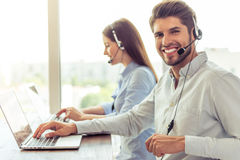 Beautiful business couple working. Side view of handsome young businessman and beautiful business women in headsets using laptops while working in office. Guy is Royalty Free Stock Photography