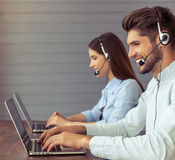Beautiful business couple working. Side view of handsome young businessman and beautiful business women in headsets using laptops and smiling while working in Royalty Free Stock Photo