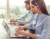 Beautiful business couple working. Side view of beautiful young business women and handsome businessman in headsets using laptops while working in office Stock Photo
