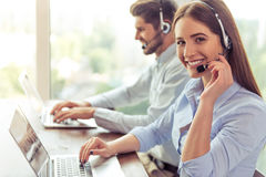 Beautiful business couple working. Side view of beautiful young business women and handsome businessman in headsets using laptops while working in office. Girl Stock Photography