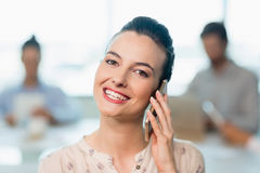 Beautiful business executive talking on her mobile phone in conference room Royalty Free Stock Photos