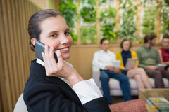 Beautiful business executive talking on her mobile phone while sitting in office lobby. Portrait of beautiful business executive talking on her mobile phone Stock Photo