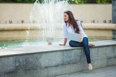 Beautiful business girl brunette sitting with laptop at a fountain in the street royalty free stock image