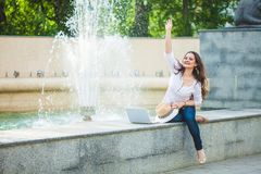 Beautiful business girl brunette in a straw hat, with a laptop at a fountain in the street and waving her hand stock photography