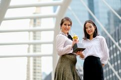Beautiful business girls show their trophy of the success in her works and stand among the high building in the city stock images