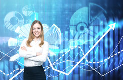 A beautiful business lady with crossed hands is going to provide financial services. Financial charts on the background. royalty free stock image