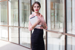 Beautiful business lady is holding tablet. Near office windows Royalty Free Stock Photography