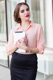 Beautiful business lady is holding tablet. Beautiful business lady with red lips is holding tablet near office windows Royalty Free Stock Photo