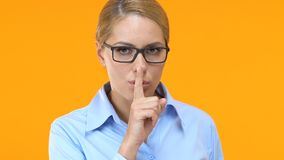 Beautiful business lady showing silence sign and winking, corporative secret