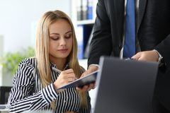 Beautiful business lady signing documents. Portrait of serious businesswoman working in office. Man holding paper folder with contract and partner underwriting stock images