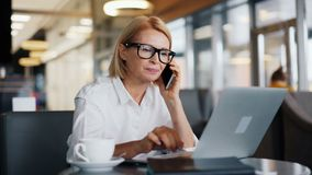 Beautiful business lady talking on mobile phone and working with laptop in cafe. Beautiful business lady in trendy glasses is talking on mobile phone and working stock footage