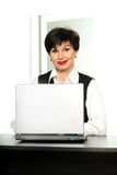 Beautiful business woman. Beautiful smiling woman with a laptop at the table royalty free stock images
