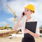 Beautiful business woman architect in builder helmet talking by Royalty Free Stock Image