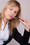 Beautiful business woman with ballpen in mouth Royalty Free Stock Photo