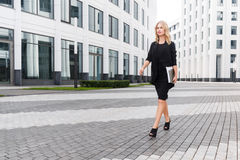 Beautiful business woman in black suit goes with laptop Stock Photos