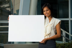 Beautiful Business Woman Blank Sign Horizontal. A cheerful beautiful young business woman holds a blank sign in horizontal position for custom text insertion Royalty Free Stock Photo