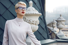 Beautiful business woman blond glasses makeup architecture. Beautiful sexy young business woman blond hair evening makeup wearing dress suit top  skirt high Stock Image